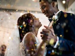 Newlywed couple dancing under confetti